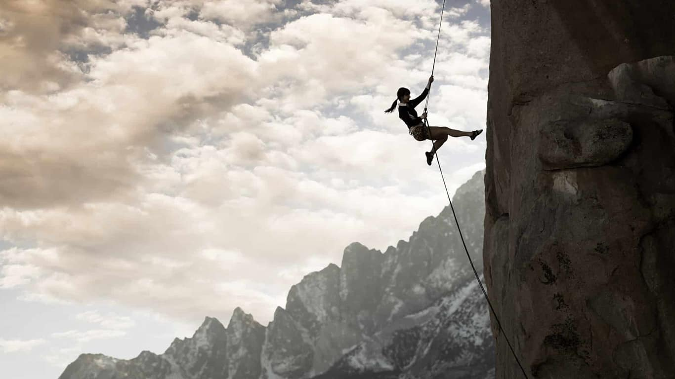 A woman rock climber rappelling down a cliff in the majestic mountains.