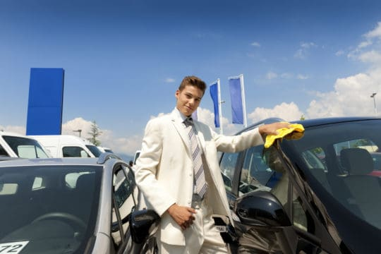 Car salesman shining a new car to finance with yellow cloth, dressed in a white suit.