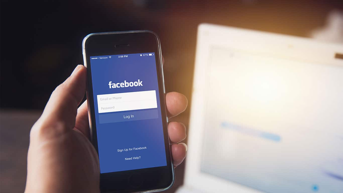 Facebook App on iPhone with computer laptop background