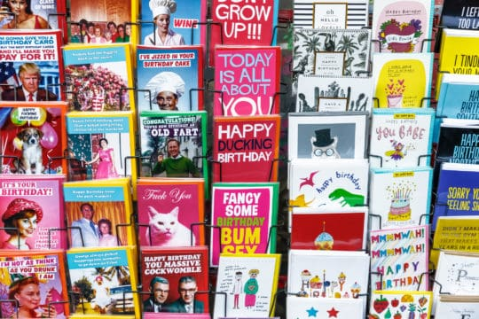 Quirky and cheap birthday cards on display at grocery store.
