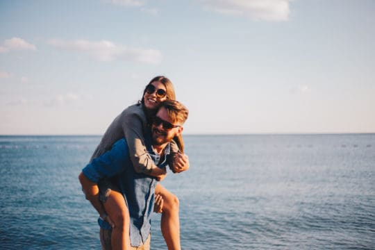 Modern couple on the beach hugging and loving each other prepared for retirement