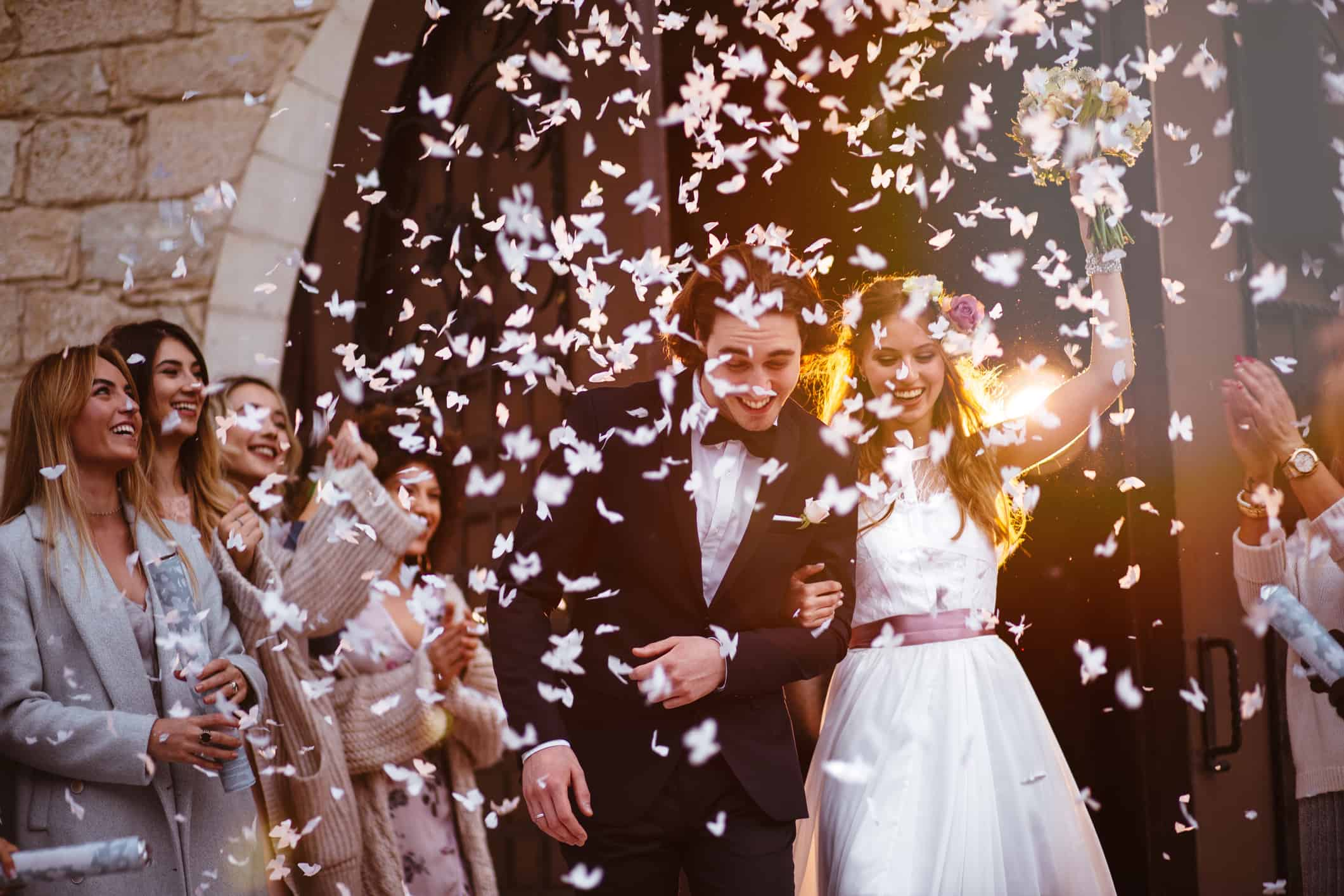 Newlywed husband and wife walking out of church and celebrating marriage with guests throwing confetti on their way to their home