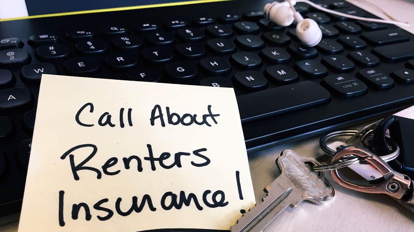 Renters insurance written on a post note, keys resting om desk, and keyboard in background