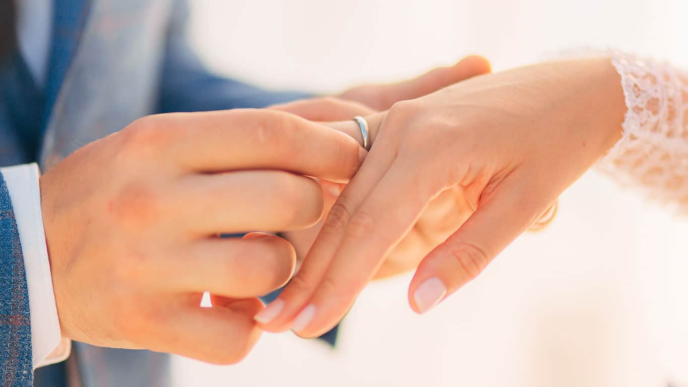 The newlyweds exchange rings at a wedding