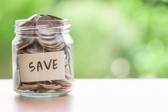 Save money on your insurance coverage. Photo of coins in glass jar for money saving financial concept