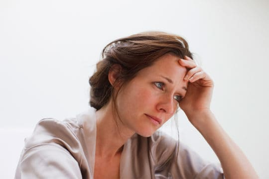Woman with head in hands feeling anxiety and depression over finances.