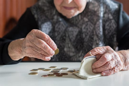 Because of unequal pay an Elderly woman counting money. unequal pay affects women's retirement in a bad way.