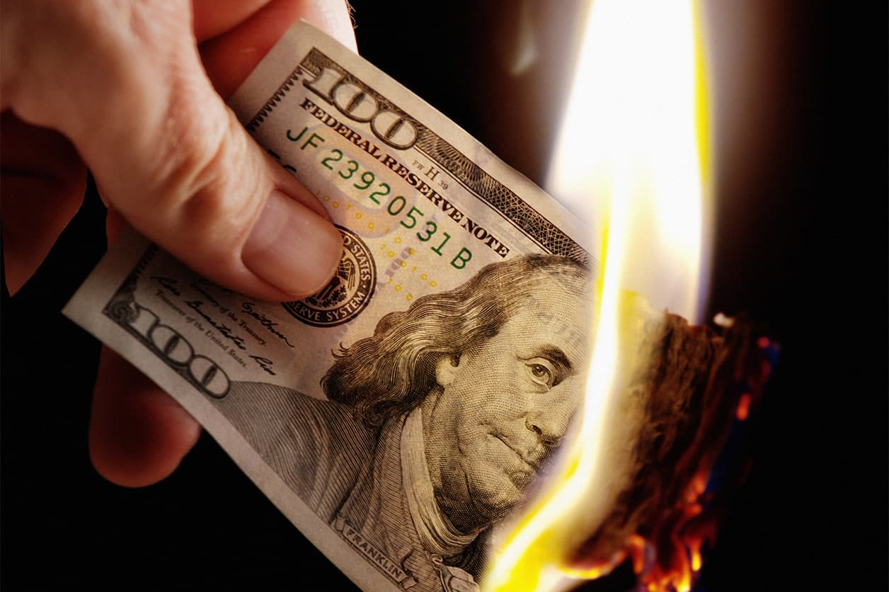Holds burning American hundred dollar. How to reduce spending and save money.