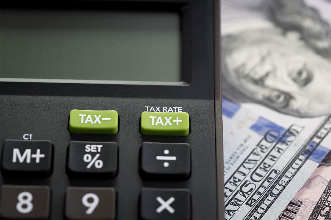 How Long Should I Keep Receipts For Tax Purposes? TAX RATE on calculator with background of blurred US Dollar banknotes.