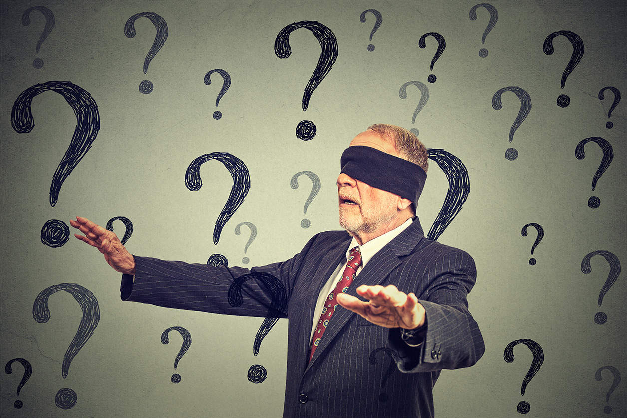 Blindfolded business man walking through many questions. Knowing how to save money on credit card interest isn't going to save you money. This represents how not paying attention means you overpay.