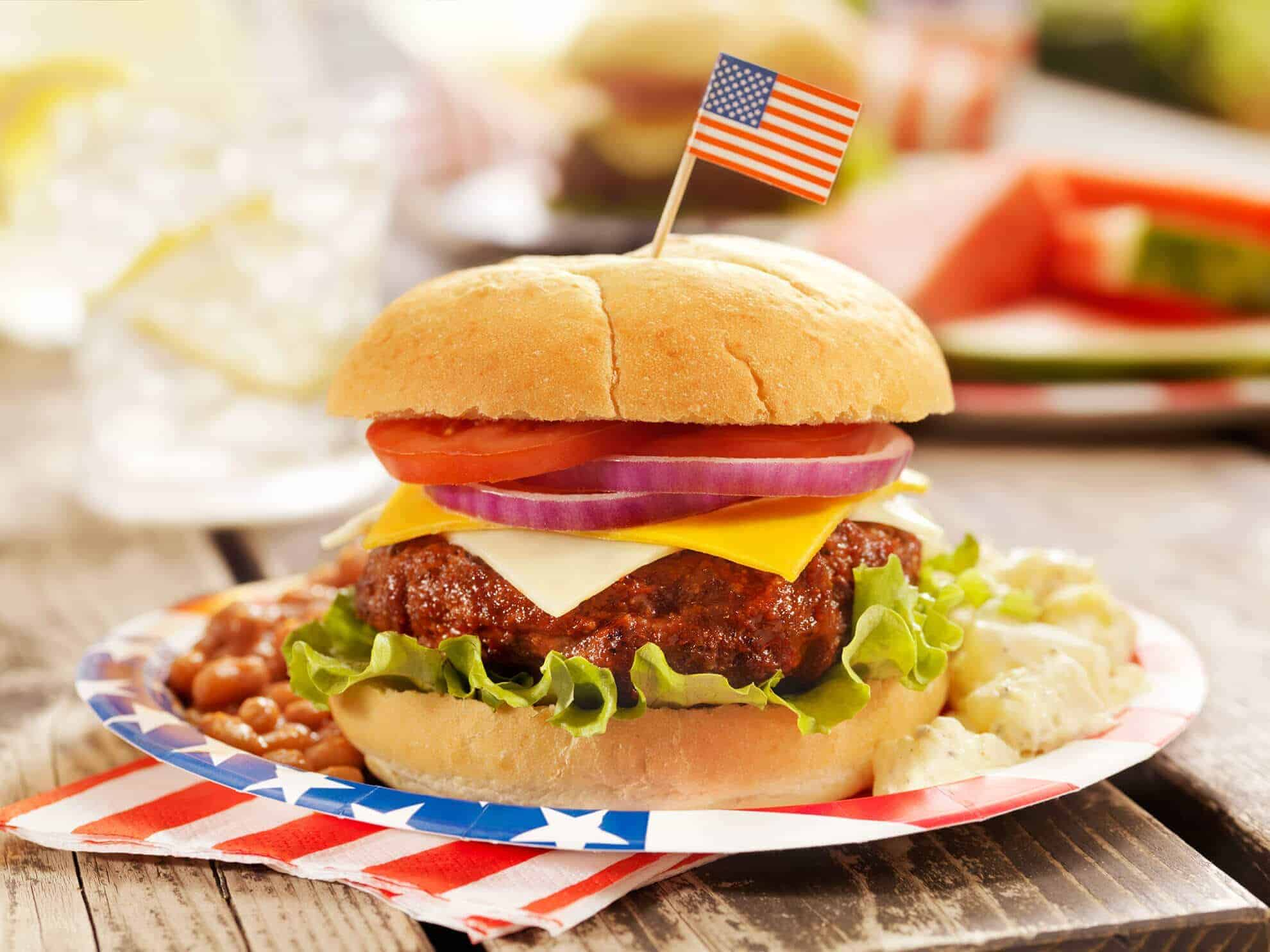 An all-American cheeseburger with lettuce, tomato, pickles, an American flag toothpick on an America plate with an America napkin