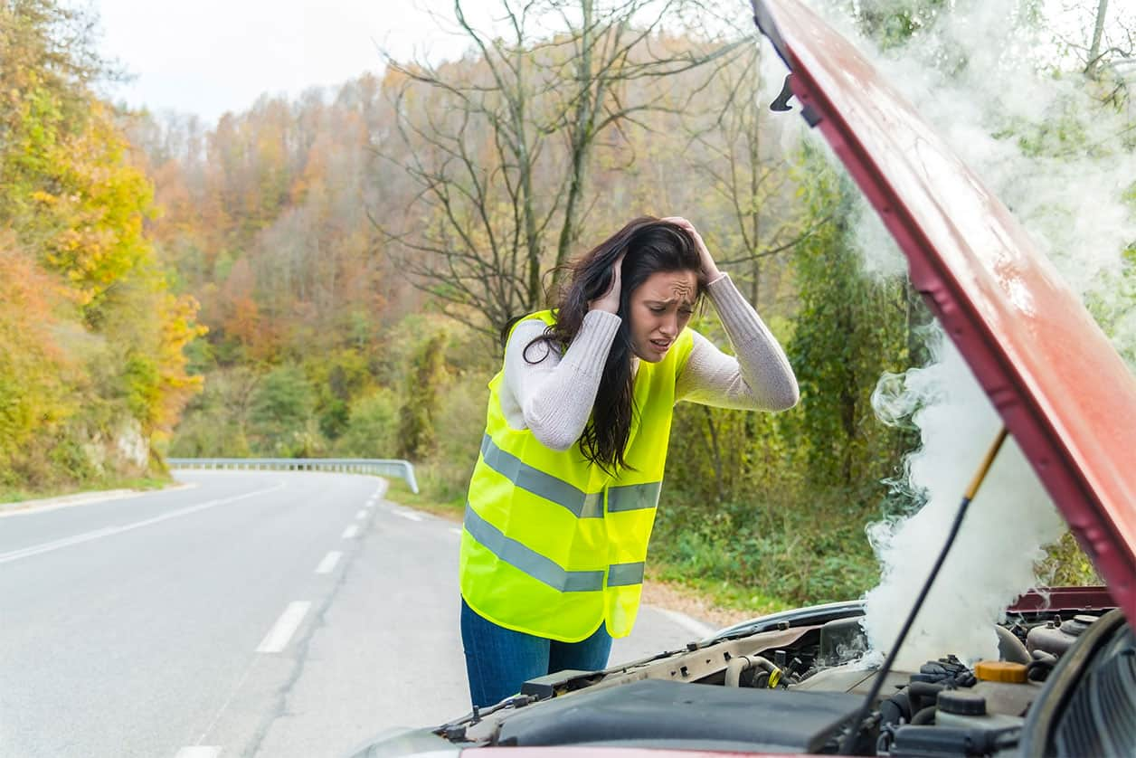 Young woman standing by her broken car on the road