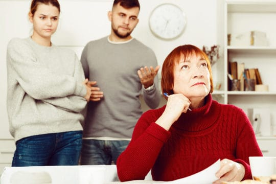Do you inherit your parents medical debt? Distressed aged woman with paperwork and irritated family behind.