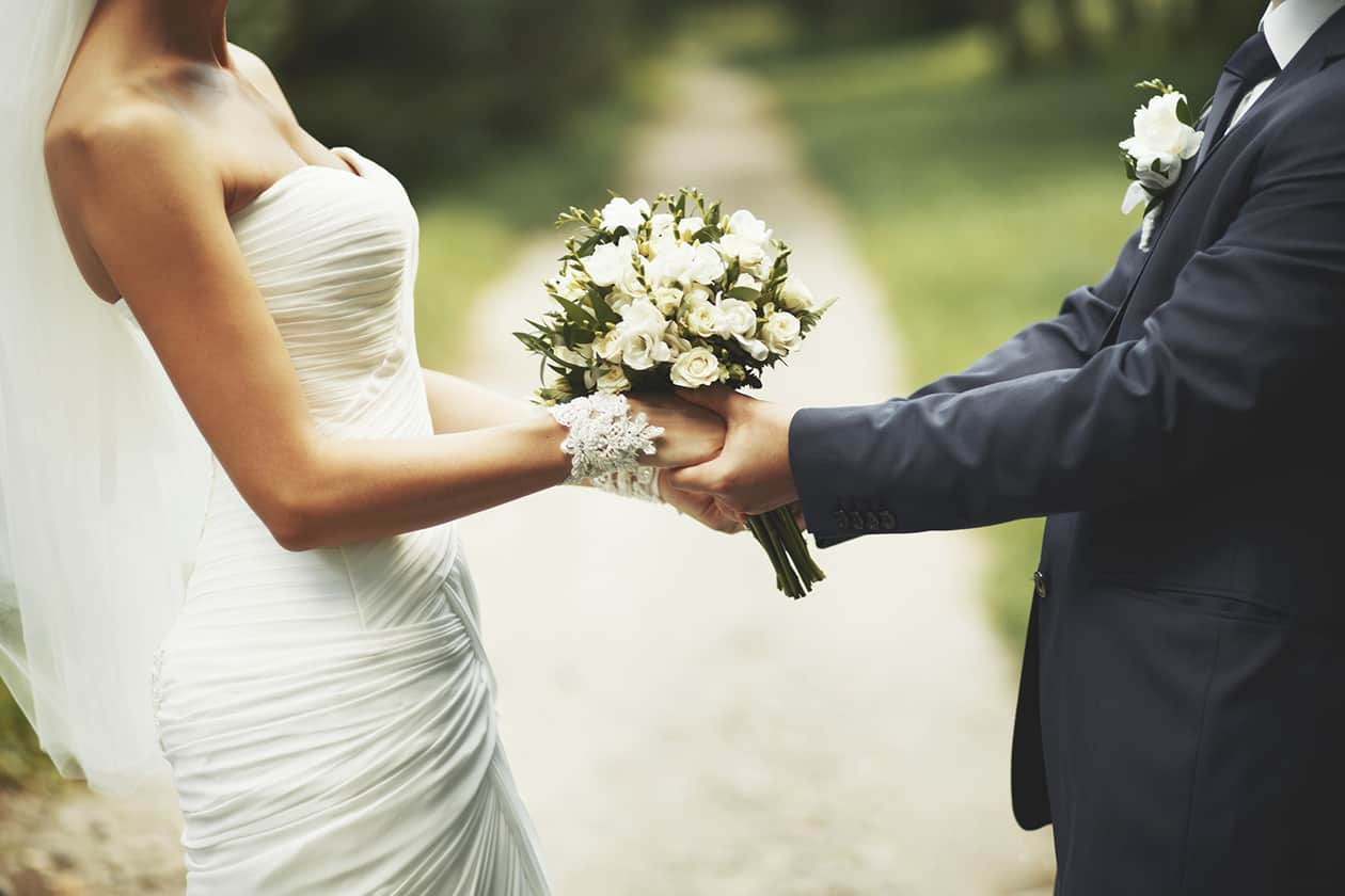Photo of couple holding hands as they tie the knot