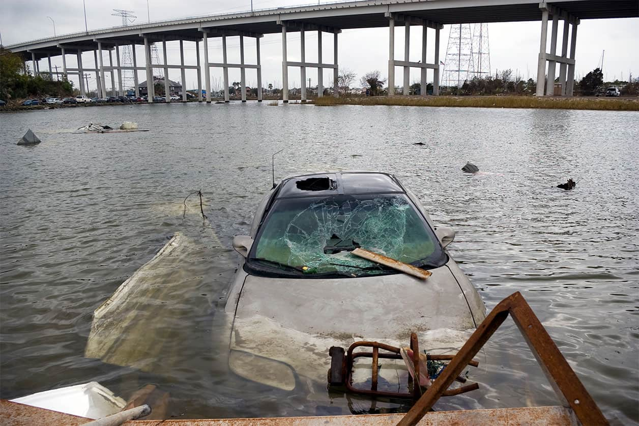 A flood damage car sits hopelessly submerged near an overpass