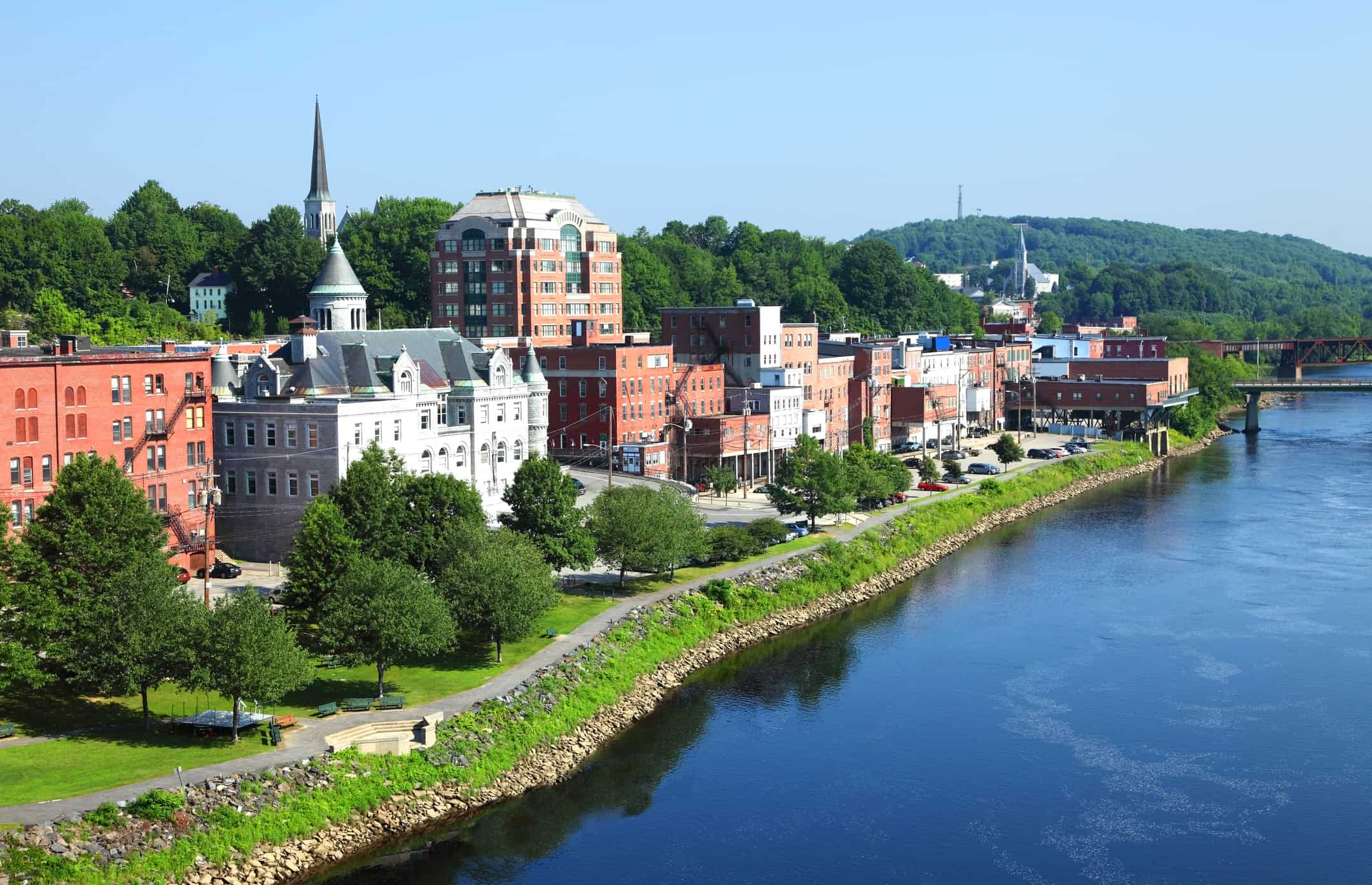 Augusta downtown skyline along the banks of the Kennebec River at night. Augusta is the capital of the U.S. state of Maine located in the Kennebec Valley. The Augusta area is known for its historic buildings, beautiful forested hills, cross-country skiing, and scenic lakes and streams