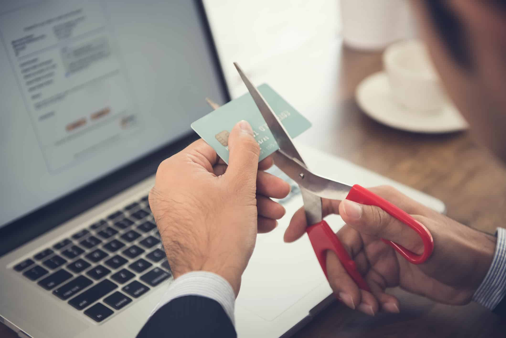 Businessman cutting a credit card that canceled by financial institute due to negligent usage