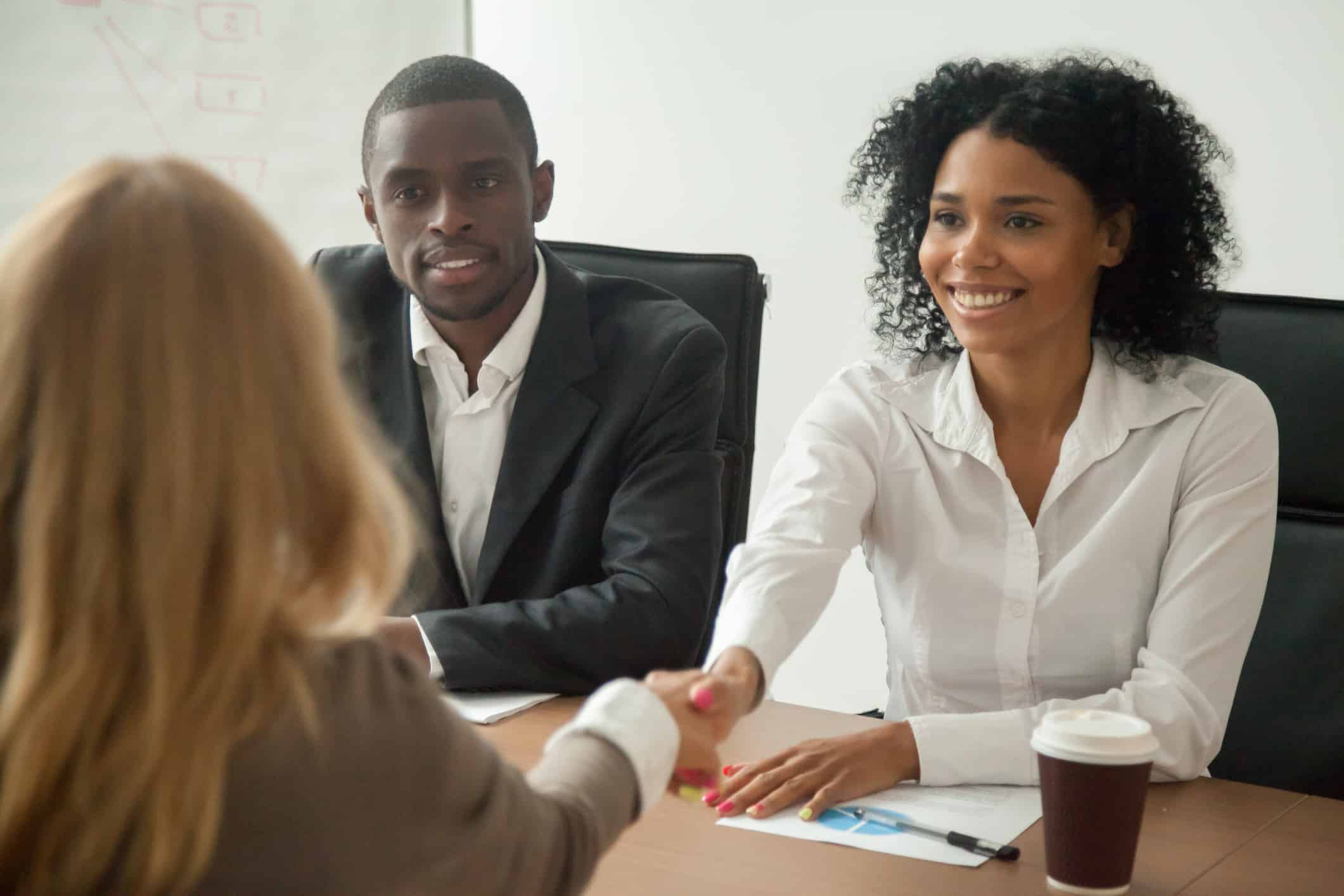 African american hr team welcoming female applicant at job interview.