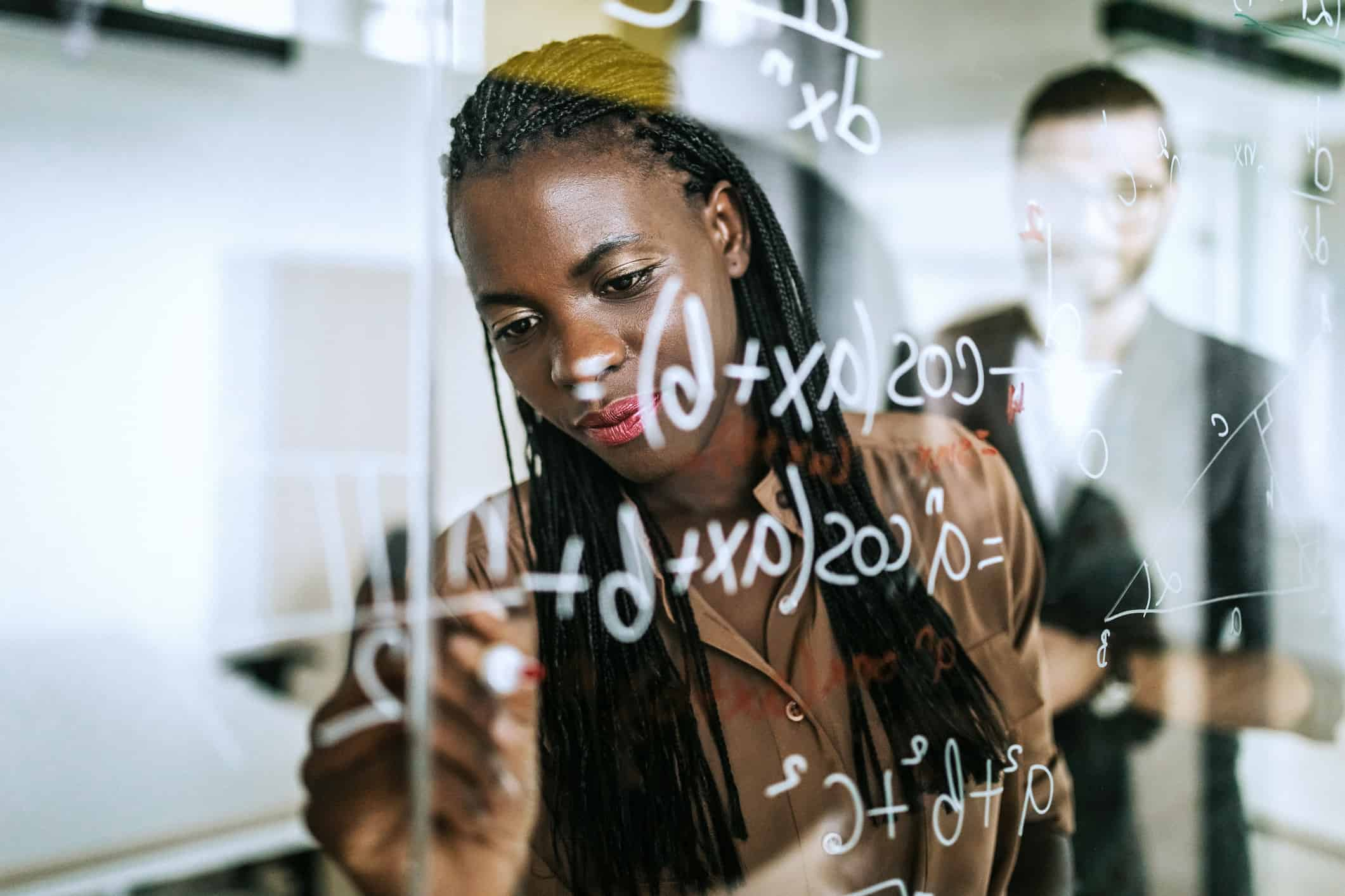 Colleagues Writing Mathematical Formulas On Transparent Wipe Board