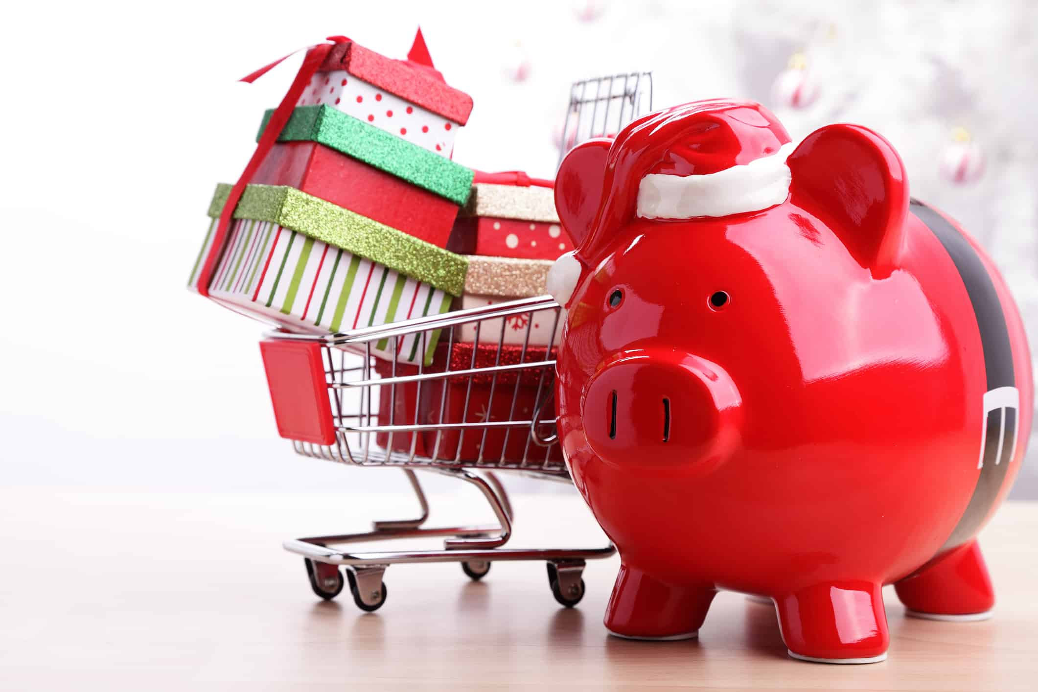 Saving money during the holidays: Red piggy bank with Santa Claus belt.