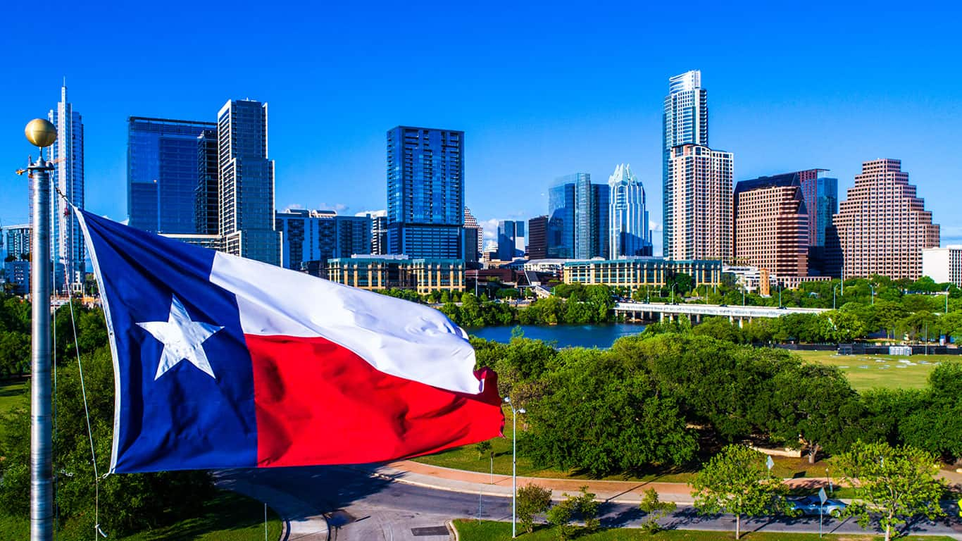 Texas flag flying in front of Austin Texas downtown skyline cityscape