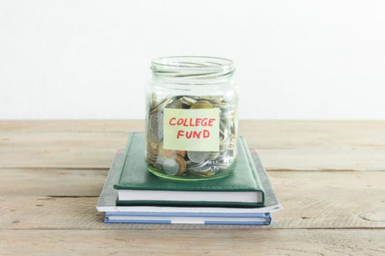 Coins in glass jar with College Fund label and books. Money savings, education or college fund, planning concept, copy space.