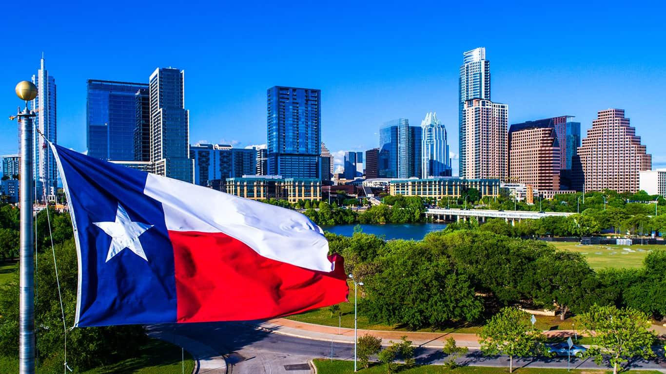 Perfect Texas flag flying in front of Austin Texas downtown skyline cityscape sunny perfect day